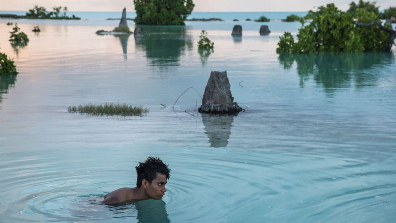 """On 26 October 2014, Peia Kararaua, 16, swims in the flooded area of Aberao village in Kiribati. Kiribati is one of the countries most affected by sea level rise. During high tides many villages become inundated making large parts of them uninhabitable.....On 22 March 2017, a UNICEF report projects that some 600 million children – or 1 in 4 children worldwide – will be living in areas where water demand far outstrips supply by 2040. Climate change is one of the key drivers of water stress, which occurs when more than 80 per cent of the water available for agriculture, industry and domestic use is withdrawn annually. According to the report """"Thirsting for a Future"""", warmer temperatures, rising sea levels, increased floods, droughts and melting ice affect the quality and availability of water. Population growth, increased water consumption, and an even higher demand for water largely due to industrialization, are also draining water resources worldwide, forcing children to use unsafe water, which exposes them to potentially deadly diseases like cholera and diahrroea. The poorest and most vulnerable children will be most impacted, as millions of them already live in areas with low access to safe water and sanitation. The impact of climate change on water sources is not inevitable, the report says, citing a series of recommendations that can help curb its effect on the lives of children."""