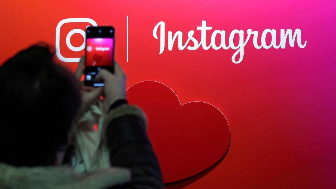A visitor takes a picture of the Instagram application logo. Image: Reuters